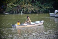 用浆划有家庭的一条小船在公园 库存图片