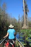 用浆划沼泽妇女的独木舟okefenokee 免版税图库摄影