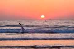 用浆划海洋日出天际的海浪滑雪独木舟 免版税库存图片