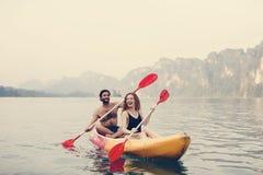 用浆划独木舟的夫妇在湖 免版税库存图片