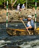 用浆划白浪独木舟的人 图库摄影