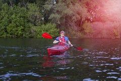 用浆划皮船的人背面图在有妇女的湖在背景中 在湖结合划皮船在一个晴天 免版税库存图片