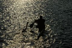 用浆划舷外架皮船的花花公子入日落 免版税图库摄影