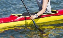 用浆划通过水急流的女性皮艇特写镜头 免版税库存照片