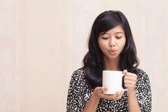 吹一个热的饮料的美丽的亚裔女孩 库存图片