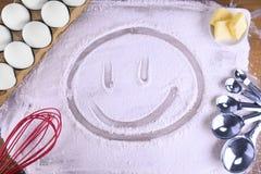 用烹调面粉做的愉快的面孔在一张木桌 库存图片