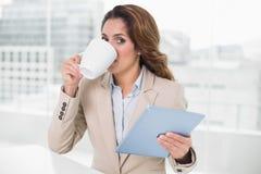 用片剂饮用的咖啡的女实业家看照相机 免版税库存照片