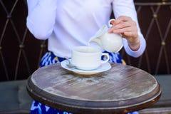 用牛奶更好品尝 更加健康咖啡喝的技巧 递加倾吐的牛奶的女性到无奶咖啡户外 图库摄影