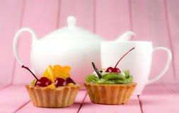 用猕猴桃、桔子、糖煮的樱桃和巧克力做的五颜六色的果子蛋糕在与茶壶和杯子的桃红色背景 免版税库存照片