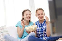 用玉米花在家看电视的愉快的女孩 库存照片