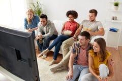 用玉米花在家看电视的愉快的朋友 库存照片