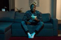用玉米花在手上看电视的被集中的非裔美国人的人 库存图片