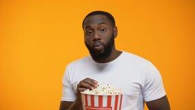 用玉米花殷勤地观看有趣的电视的非裔美国人的人 股票录像