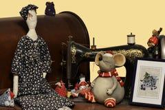 用玩偶、老鼠和被绣的图片装饰的古色古香的缝纫机 库存照片
