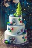 用玩具熊图画装饰的圣诞节五颜六色的三层蛋糕,礼物盒和一棵绿色树冠上 库存照片