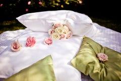 用玫瑰和枕头装饰的毯子 库存照片