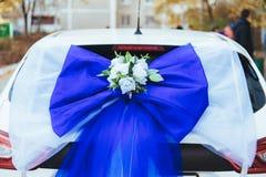 用玫瑰装饰的一辆黑婚礼汽车 用花和丝带装饰的豪华婚礼汽车 免版税库存图片