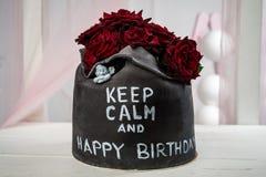 用玫瑰装饰的可口手工制造蛋糕,与题字kep kalm和napa生日 水平的框架 库存图片