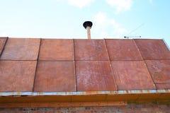 用生锈的金属板料盖的乡间别墅的屋顶  免版税库存图片