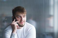 用电话讲话在墙壁的背景的办公室一个美丽的人的画象白色衣裳的 免版税图库摄影