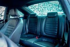 用皮革包盖在小轿车跑车里面的后面乘客座位 库存图片