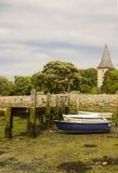 用眼镜和海草盖的一只小木跳船在港口在Bosham村庄在英国的南部的西部苏克塞斯 免版税库存图片