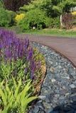 用石头和花装饰的木道路 库存照片