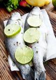 用石灰切片和干胡椒晒干的未加工的鳟鱼 免版税库存照片