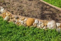 用石头扶植的空的花床 库存图片