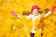 用秋叶盖的愉快的微笑的女孩 库存照片