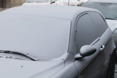 用第一雪盖的停放的汽车在冬天 免版税图库摄影