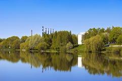 用管道输送横跨河的老工厂。 库存图片