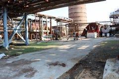 用管道运输与铁管子的天桥抽的液体的以一个大砖烟管子为背景在炼油厂, petroc 免版税库存图片
