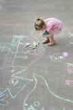 用粉笔写在跳房子围场的小白种人女孩顶上的射击  免版税库存照片