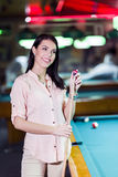 用粉笔写落袋撞球暗示和微笑的年轻美丽的妇女 库存图片