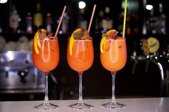用糖面包屑装饰的三个橙色冷的鸡尾酒,切片桔子和薄菏 库存图片