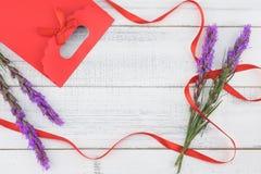 用紫罗兰色鹿舌草装饰的红色礼物袋子开花 库存照片
