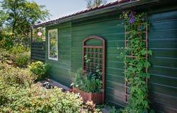 用紫色铁线莲属装饰的庭院棚子 图库摄影