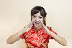 用繁体中文或cheongsam的亚洲妇女问候与手推力欢迎表示和幸运和在春节享用 图库摄影
