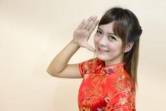 用繁体中文或cheongsam的亚洲妇女问候与手推力欢迎表示和幸运在春节celebrati 免版税库存照片