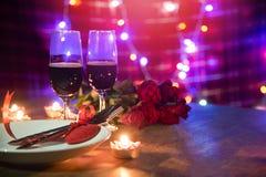 用红心在板材和夫妇香槟的叉子匙子装饰的华伦泰晚餐浪漫爱概念浪漫桌设置 免版税库存图片