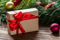 用红色丝绸条纹装饰的精密圣诞节礼物盒宏指令,在与圣诞节的被弄脏的杉树背景 图库摄影