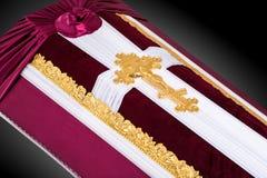 用红色和白色布料盖的闭合的棺材装饰用教会在灰色豪华背景的金十字架 特写镜头 免版税库存图片