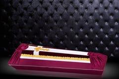 用红色和白色布料盖的闭合的棺材装饰用教会在灰色豪华背景的金十字架 图库摄影