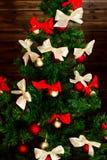 用红色和米黄色的缎弓装饰的聪明的圣诞树 免版税库存照片
