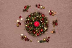 用红色和金子圣诞节装饰装饰的新鲜的手工制造圣诞节花圈,冷杉锥体和核桃与一个灼烧的红色蜡烛 免版税图库摄影