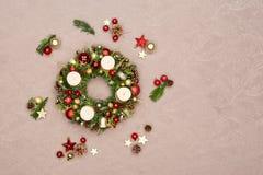 用红色和金子圣诞节装饰装饰的新鲜的手工制造圣诞节花圈,冷杉锥体和核桃与四烧加州的金子 免版税图库摄影