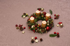 用红色和金子圣诞节装饰装饰的新鲜的手工制造圣诞节花圈,冷杉锥体和核桃与金蜡烛 免版税库存照片