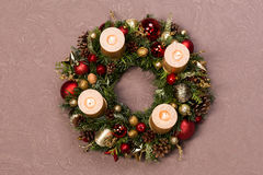 用红色和金子圣诞节装饰装饰的新鲜的手工制造圣诞节花圈,冷杉锥体和核桃与金蜡烛 库存照片