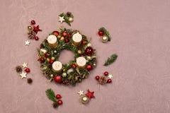 用红色和金子圣诞节装饰装饰的新鲜的手工制造圣诞节花圈,冷杉锥体和核桃与金蜡烛 免版税图库摄影